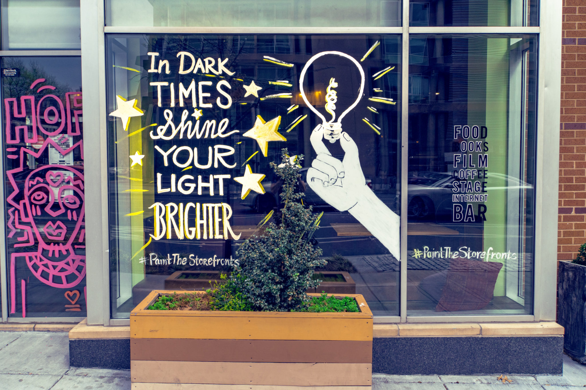 """window at busboys and poets in washington reads """"in dark times, shine your light brighter"""""""